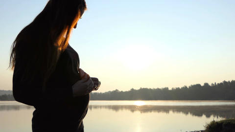 a Pregnant Woman Plays With Slippers For Her Baby on a Lake Bank in 4K Live Action