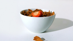 Strawberry falling in a wheat cereals bowl Footage