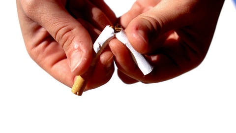 Feminine hands cutting a cigarette in half Live Action