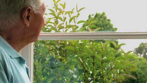 Senior man looking at window Footage