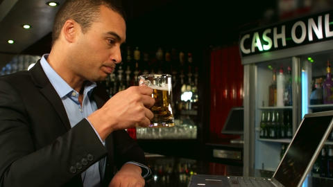 Businessman having a beer and using laptop Footage