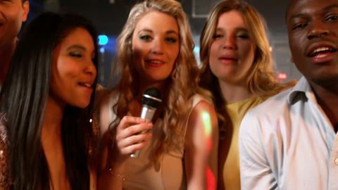 Happy friends singing at the karaoke in night club Live Action