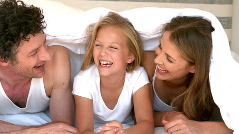 Cute family hiding on their bed Footage