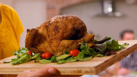 Feminine hands bringing a chopping board with the chicken on it Live Action
