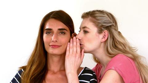 Woman telling secret to her friend Footage