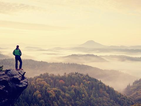 Man stay on rocky peak within daybreak and watch over misty landscape Photo