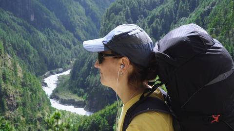 girl listening to music with headphones on a background of mountains Footage