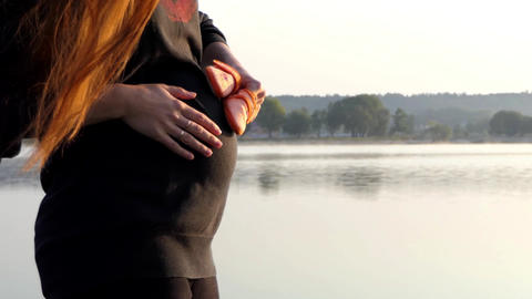 a Cheery Pregnant Woman Plays With Baby's Slippers at Sunset in Autumn in Slo-Mo Footage