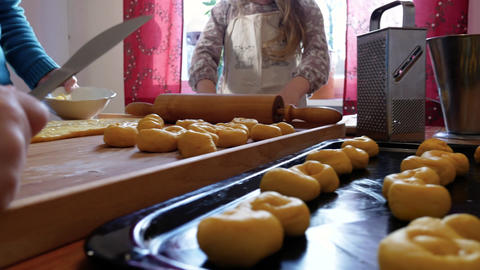 A young boy and a girl bakes saffron buns with their grandmother Footage