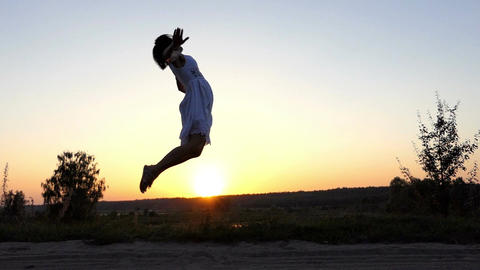 Happy Woman Jumps in The Air, Touches Her Heels, at a Nice Sunset in Slo-Mo Footage