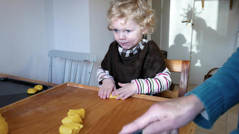 A little boy and his grandmother are baking in the kitchen Footage