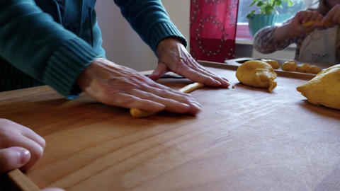 Grandmother helps her grandchild to roll the dough Footage