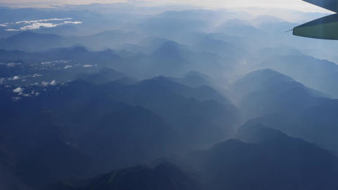 Beautiful view through airplane window, airplane flying above river in mountains Live Action