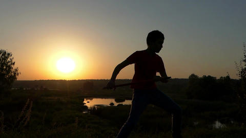 Small Boy Strikes Kung-Fu Blows on a Lake Bank at Sunset in Autumn in Slo-Mo Footage