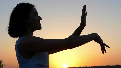 a Young Slim Woman Does Waving Movements With Her Hands at Sunset in Slo-Mo Live Action