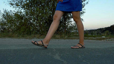 Female legs walk on a road near a lake in summer in slo-mo Footage
