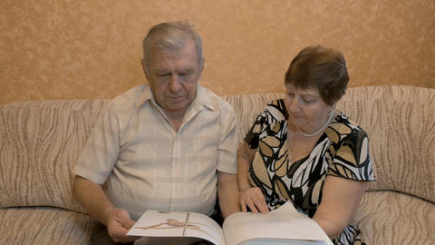 Elderly couple reading a book, on the couch, they are happy together Footage