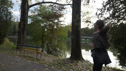 Girl with slender figure jogging on an alley park near the lake trying to relax Footage