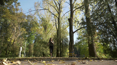 Skinny teenager girl jogging in the park while leaves fall from the trees on a Footage