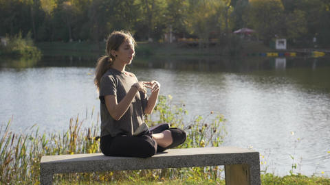 Beautiful young student girl doing yoga outdoor in nature and meditating in Footage