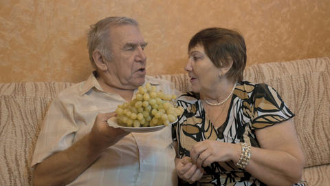 An adult couple eat grapes, and feed each other. close-up Footage