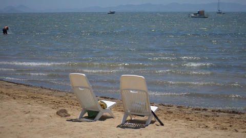 Two Empty Plastic Chairs On The Beach 画像
