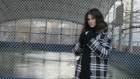 Woman in coat near net fence ビデオ