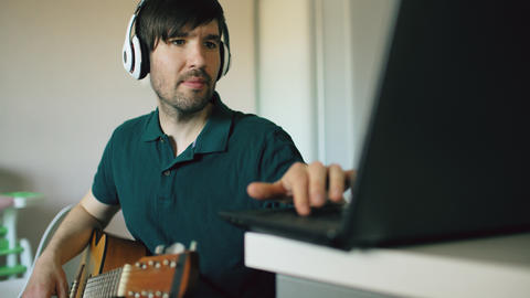 Cheerful young man with headphones sitting at kitchen learning to play guitar フォト