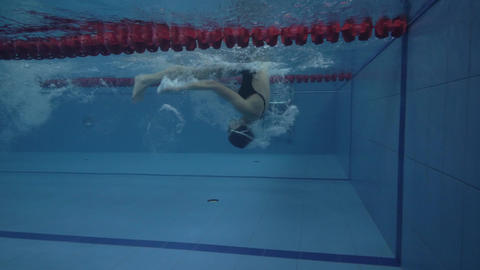 Female professional swimmer floating crawl stroke in pool and turning underwater ビデオ
