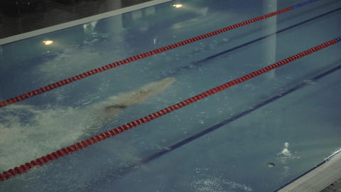 Sports woman swimmer diving in clear water in empty swimming pool slow motion Footage
