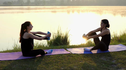 Two Young Women Practice Yoga Sitting on Mats on a Lake Bank at Sunset in Slo-Mo Footage