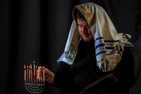 Hanukkah, a Jewish celebration. Candles burning in the menorah, man in the Foto