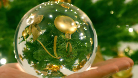Decorated Christmas tree as seen through the glass ball in the hand Footage