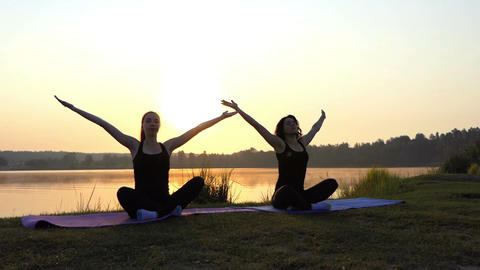 Two Girls Sit on Mats in Semi-Lotus Pose on a Lake Bank at Sunset in Slo-Mo Footage