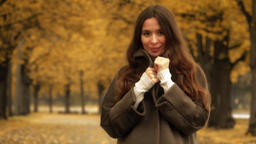 Beautiful young brunette wearing coat looks at the camera on autumn alley 画像
