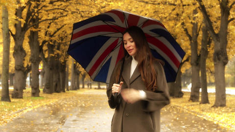 Beautiful young woman standing with umbrella on autumn alley on a rainy day Footage