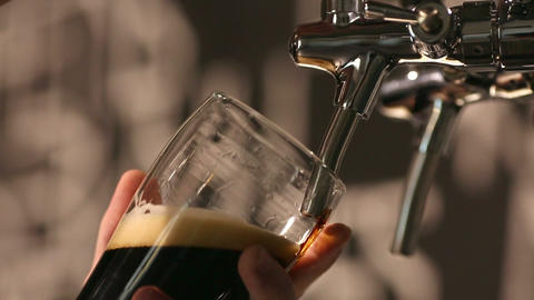 The bartender pours a dark beer in glass close-up Footage