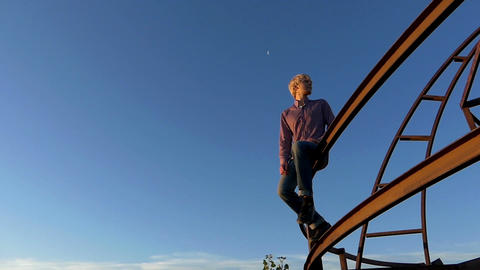 Romantic man sits on a metallic construction at sunset in slo-mo Archivo