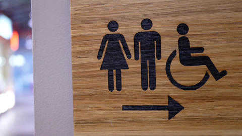 Motion of wooden man and woman washroom logo on wall inside Burnaby shopping Footage