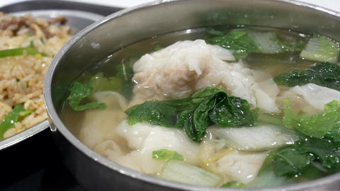 Motion of seafood dumpling soup on table inside restaurant with heavy steam Live Action