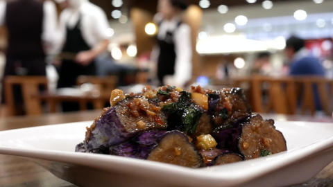 Motion of waiter serving fried eggplant on table for customer inside restaurant Footage