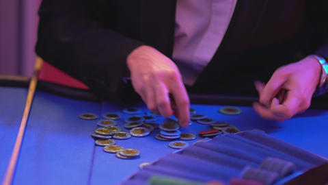Roulette table in a casino - groupier collects and sorts gaming chips Footage