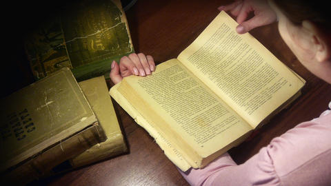 Woman turns the pages of a old books Footage