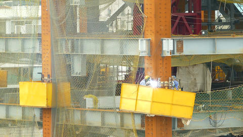 Workers arc welding on building construction site Footage