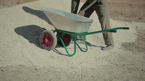 worker loads gravel into a wheelbarrow Footage