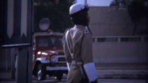 1974: Police uniform traffic officer patrolling busy street corner Footage