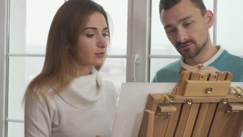 Pretty girn and handsome man draws picture together Footage