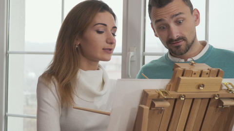 Young woman with handsome man draws picture Footage