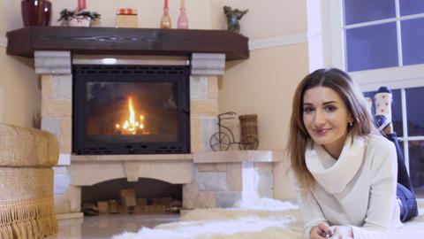 Charming blonde lays on floor near fireplace Footage