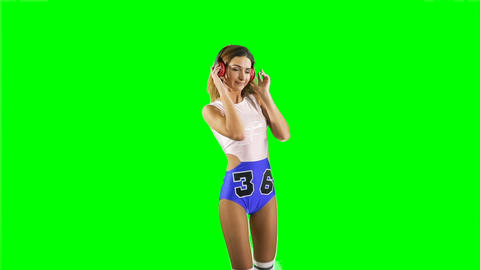 Young girl dancing to the music in headphones at chroma key background Footage